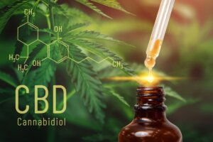 CBD oil in dropper beside molecular structure